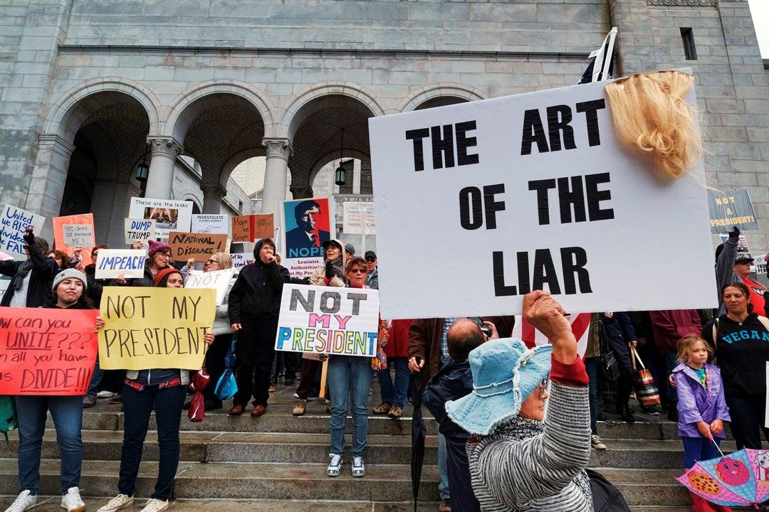 Protesters stand on the steps of Los Angeles City Hall on Monday, Feb. 20, 2017. Demonstrators gathered to express their opposition to President Donald Trump and take part in a ''Not My President's Day'' rally. (AP Photo/Richard Vogel)