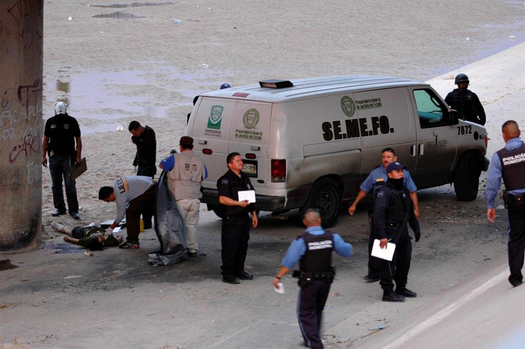 FILE - In this June 7, 2010 file photo, Mexican forensic experts examine the body of 14-year-old Sergio Adrian Hernandez Guereca under the Paso Del Norte border bridge in the city of Ciudad Juarez, Mexico. (AP Photo/File)