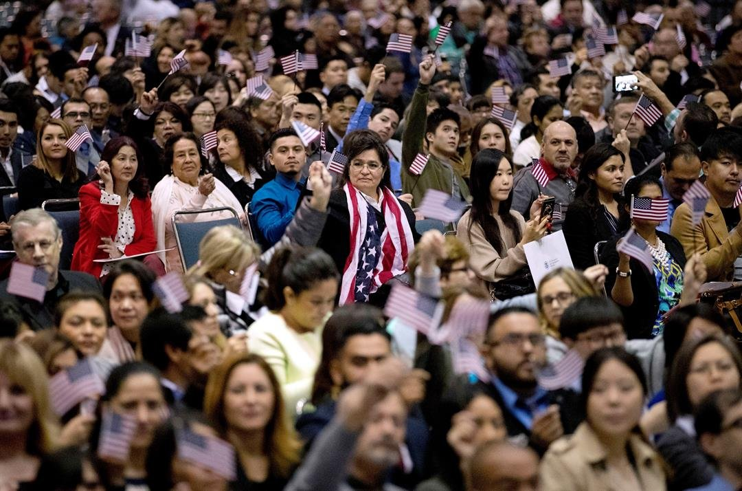 FILE - In this Wednesday, Feb. 15, 2017, file photo, people wave U.S. flags during a naturalization ceremony at the Los Angeles Convention Center, in Los Angeles. (AP Photo/Jae C. Hong, File)