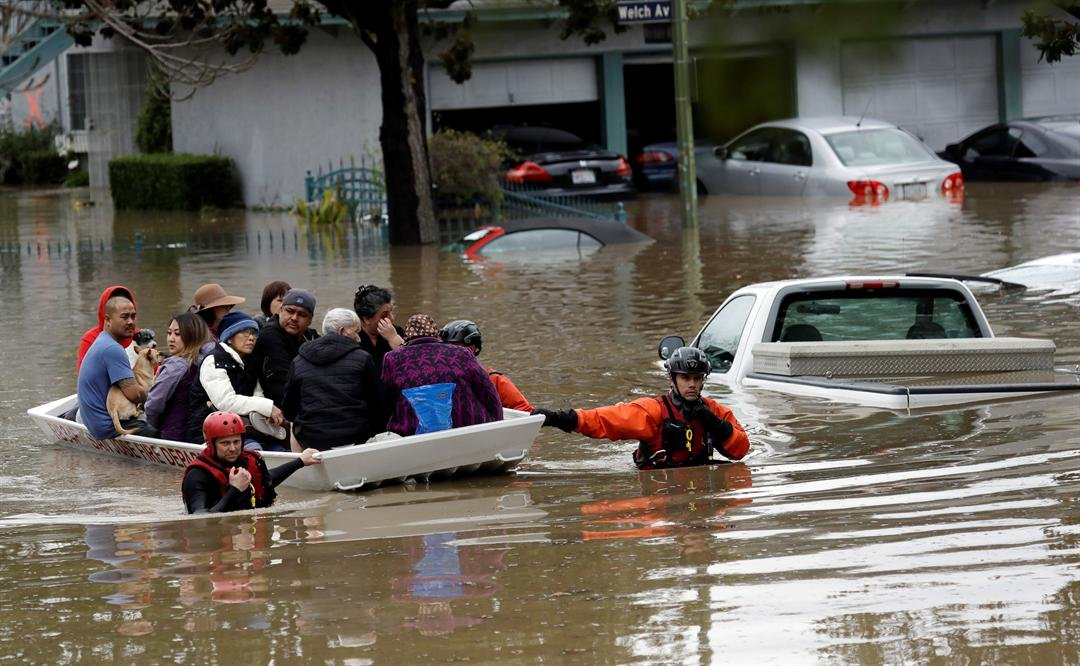 Rescuers chest-deep in water steered boats carrying dozens of people, some with babies and pets, from a San Jose neighborhood inundated by water from an overflowing creek Tuesday. (AP Photo/Marcio Jose Sanchez)