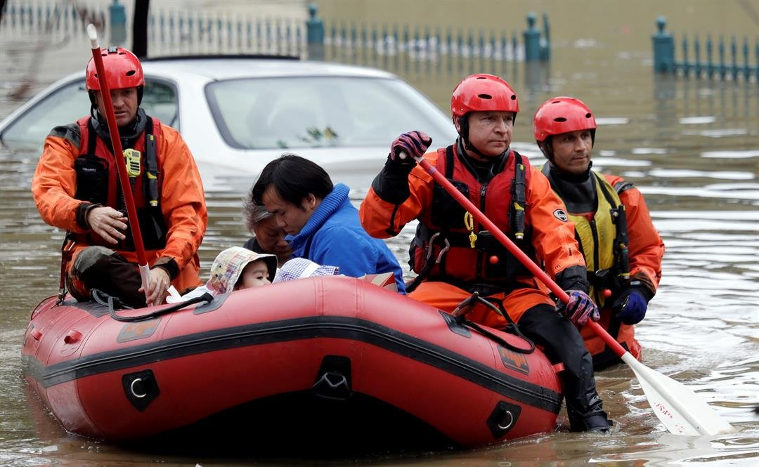 Rescue crews take out residents from a flooded neighborhood Tuesday, Feb. 21, 2017, in San Jose, Calif. Rescuers chest-deep in water steered boats carrying dozens of people, some with babies and pets, from a San Jose neighborhood inundated by water from a
