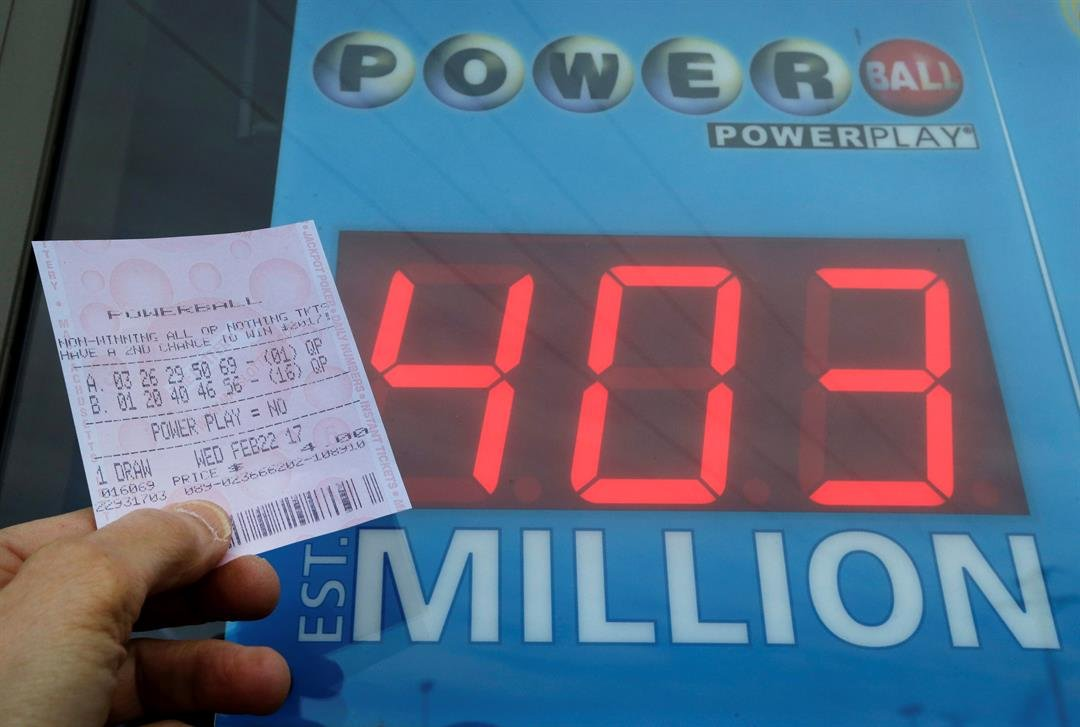 A Powerball quick-pick ticket is seen near signage displaying the jackpot amount, Wednesday, Feb. 22, 2017 (AP Photo/Elise Amendola)