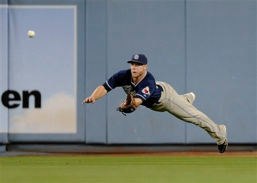 San Diego Padres right fielder Aaron Cunningham dives and catches a fly ball by Los Angeles Dodgers' Matt Kemp during the fourth inning of a baseball game, Wednesday, Sept. 22, 2010, in Los Angeles. (AP Photo/Gus Ruelas)