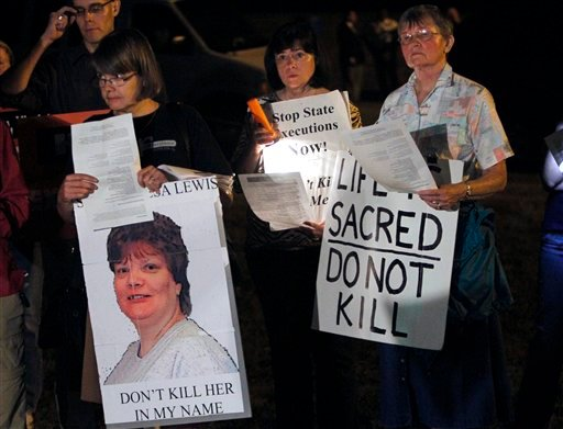 Death penalty protestors hold signs as they protest the execution of Teresa Lewis outside the Greensville Correctional Center in Jarratt, Va., Thursday, Sept. 23, 2010. Teresa Lewis was executed and pronounced dead at 9:13 p.m. (AP Photo/Steve Helber)