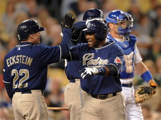 San Diego Padres' Miguel Tejada  celebrates his two-run homer with teammate David Eckstein in the third inning of a baseball game against the Los Angeles Dodgers, Wednesday, Sept. 22, 2010, in Los Angeles. (AP Photo/Gus Ruelas)