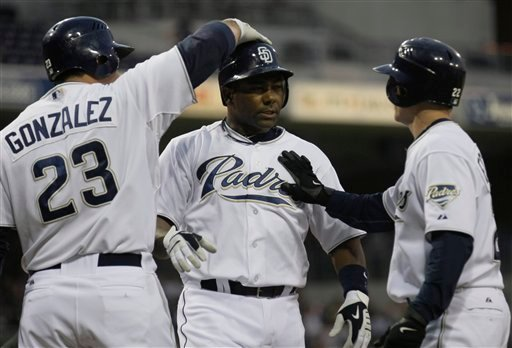 San Diego Padres' Miguel Tejada, center, is greeted by teammates Adrian Gonzalez, left, and David Eckstein, right, after hitting a two-run home run against the Arizona Diamondbacks. (AP Photo/Gregory Bull)