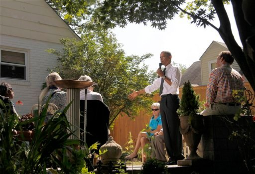 President Barack Obama, accompanied by Health and Human Services Secretary Kathleen Sebelius, center, speaks at a private residence in Falls Church, Va.