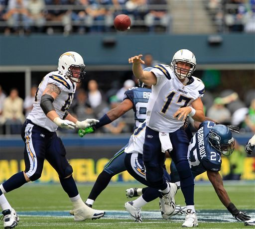 San Diego Chargers quarterback Philip Rivers passes as Chargers' Jeromey Clary looks on at left, in the first half of an NFL football game against the Seattle Seahawks, Sunday, Sept. 26, 2010, in Seattle. (AP Photo/Elaine Thompson)