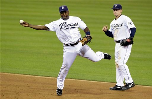 Padres shortstop Miguel Tejada, left, throws to first for the out on the Chicago Cubs' Starlin Castro in the sixth inning during their baseball game Sept. 27, 2010, in San Diego. Second baseman David Eckstein looks on at right. (AP Photo/ Gregory Bull)