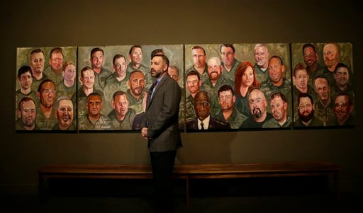 U.S. military veteran Robert Ferrara talks in front of a mural painted by Former President George W Bush during a press preview of an exhibition of Bush's paintings of veterans in Dallas, Tuesday, Feb. 28, 2017.
