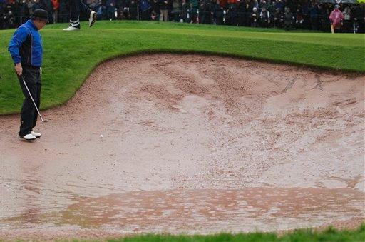 Europe's Lee Westwood looks for his ball in a bunker near the 4th green during heavy rainfall in the 2010 Ryder Cup golf tournament at the Celtic Manor golf course in Newport, Wales, Friday, Oct. 1, 2010. (AP Photo/Matt Dunham)