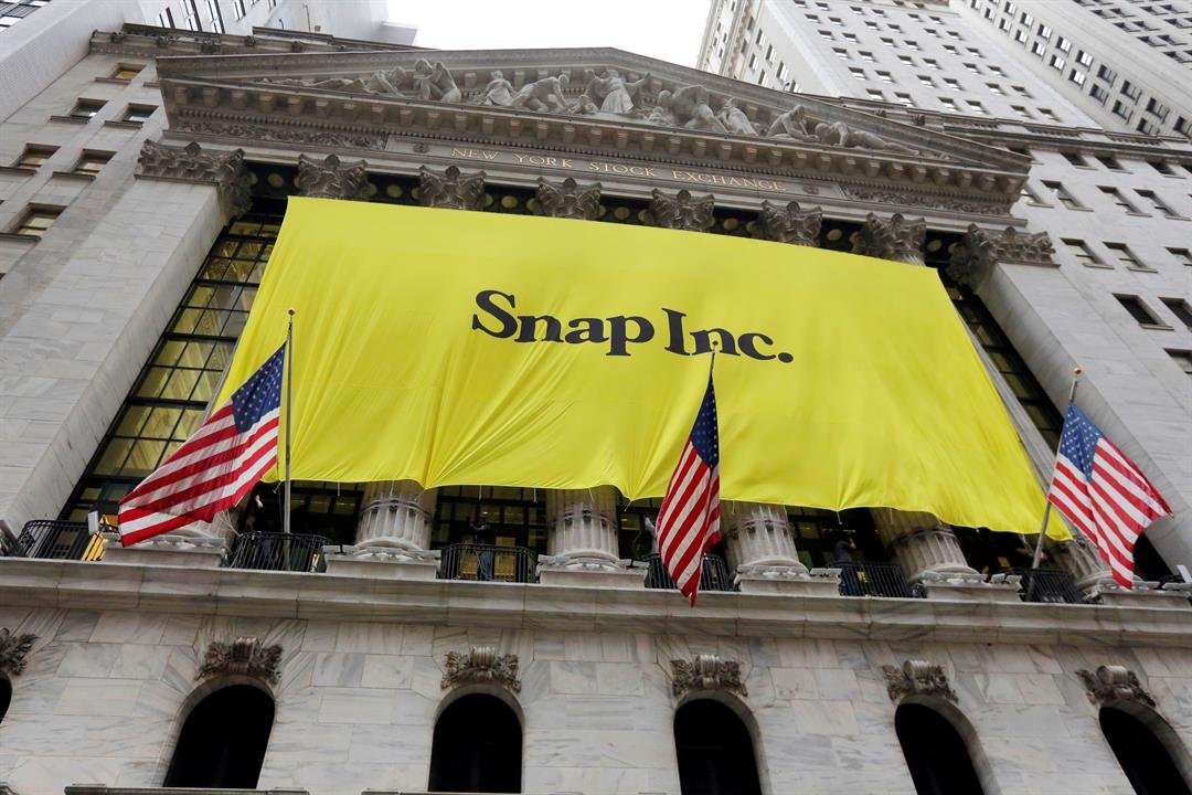 "The banner for the Snap Inc. IPO is raised on the facade the New York Stock Exchange, Wednesday, March 1, 2017. Snap Inc. is expected to start trading on the New York Stock Exchange on Thursday under the symbol ""SNAP."" (AP Photo/Richard Drew)"