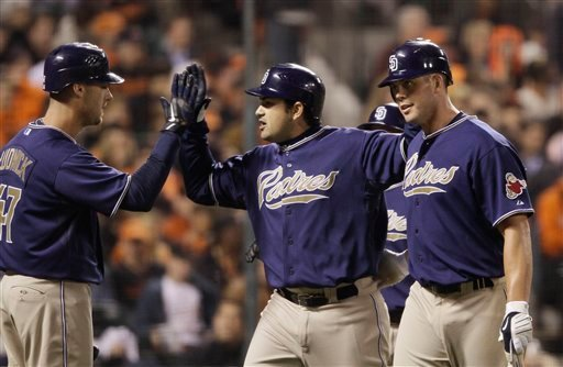 San Diego Padres' Adrian Gonzalez, center, is greeted by teammates Ryan Ludwick, left, and Clayton Richard, right, after hitting a three-run homer off San Francisco Giants starting pitcher Matt Cain during the third inning. (AP)