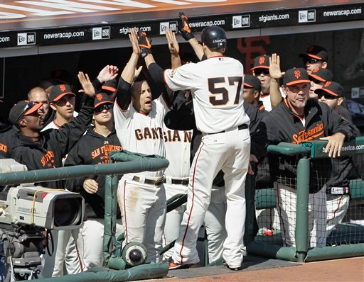 San Francisco Giants' Jonathan Sanchez (57) is greeted by in the dugout by Andres Torres and his teammates after scoring the Giants' first run in the third inning. (AP Photo/Eric Risberg)