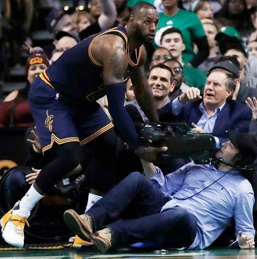 New England Patriots coach Bill Belichick, top right, watches as Cleveland Cavaliers forward LeBron James, left, collides with a televison cameraman during the fourth quarter of an NBA basketball game in Boston.