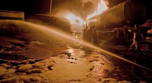 Pakistani fire fighters struggle to extinguish burning oil tankers after militants attacked a terminal in Rawalpindi, Pakistan, early Monday, Oct. 4, 2010. (AP Photo/Anjum Naveed)