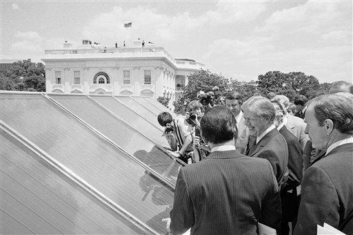 In this June 20, 1979, file photo President Jimmy Carter, center, is surrounded by reporters and photographers as he inspected new White House solar hot water heating system located on the roof of the West Wing of the mansion, over the Cabinet Room. (AP)