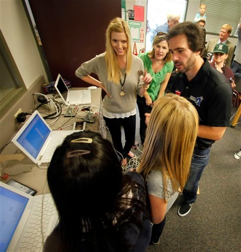 Jimmie Johnson, four-time defending NASCAR Sprint Cup Series champion, and his wife, Chandra, left, listen to students explain their science projects in a laboratory at Emerald Middle School in his hometown of El Cajon, Calif.