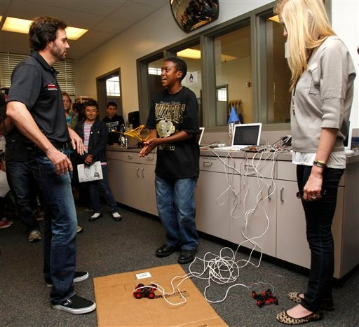 Jimmie Johnson, left, and his wife, Chandra, listen to J.T. Duboise, 13, as he explains his automated model car.