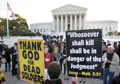Westboro Baptist Church member Jacob Phelps, of Topeka, Kan., holds signs as people engage him in front of the Supreme Court in Washington, Wednesday, Oct. 6, 2010.