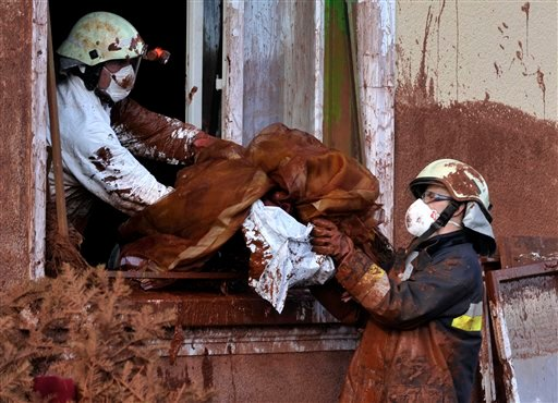 Firefighters, wearing protective gear, discard belongings from a house damaged by flooding toxic mud in the village of Kolontar, Hungary, Thursday, Oct. 7, 2010. (AP Photo/Bela Szandelszky)