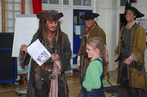 A Handout image made available by Meridian School on Friday, Oct. 8, 2010, U.S. actor Johnny Depp, left, holds a letter from 5 year old Bea Delap, right, inviting him to attend her school assembly.