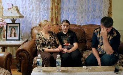 With a portrait on the side table of Sladjana Vidovic, who committed suicide in 2008, her mother Celija, left, father Dragan, and sister Suzana, talk about their loss in their home in Mentor, Ohio on Wednesday, Sept. 1, 2010.