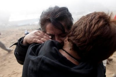 Relatives of trapped miners embrace at the San Jose Mine near Copiapo, Chile, Saturday, Oct. 9, 2010.