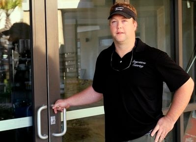 In this Oct. 8, 2010 photo, Chef Chris Sherrill, owner of Staycations Beach Weddings, stands outside the storefront he planned to open before the oil spill slowed business this summer, in Gulf Shores, Ala.