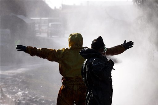 Hungarian soldiers wearing protective gear are washed by water jets in Devecser, 164 kms southwest of Budapest, Hungary, Saturday Oct. 9, 2010. (AP Photos/MTI, Lajos Nagy)