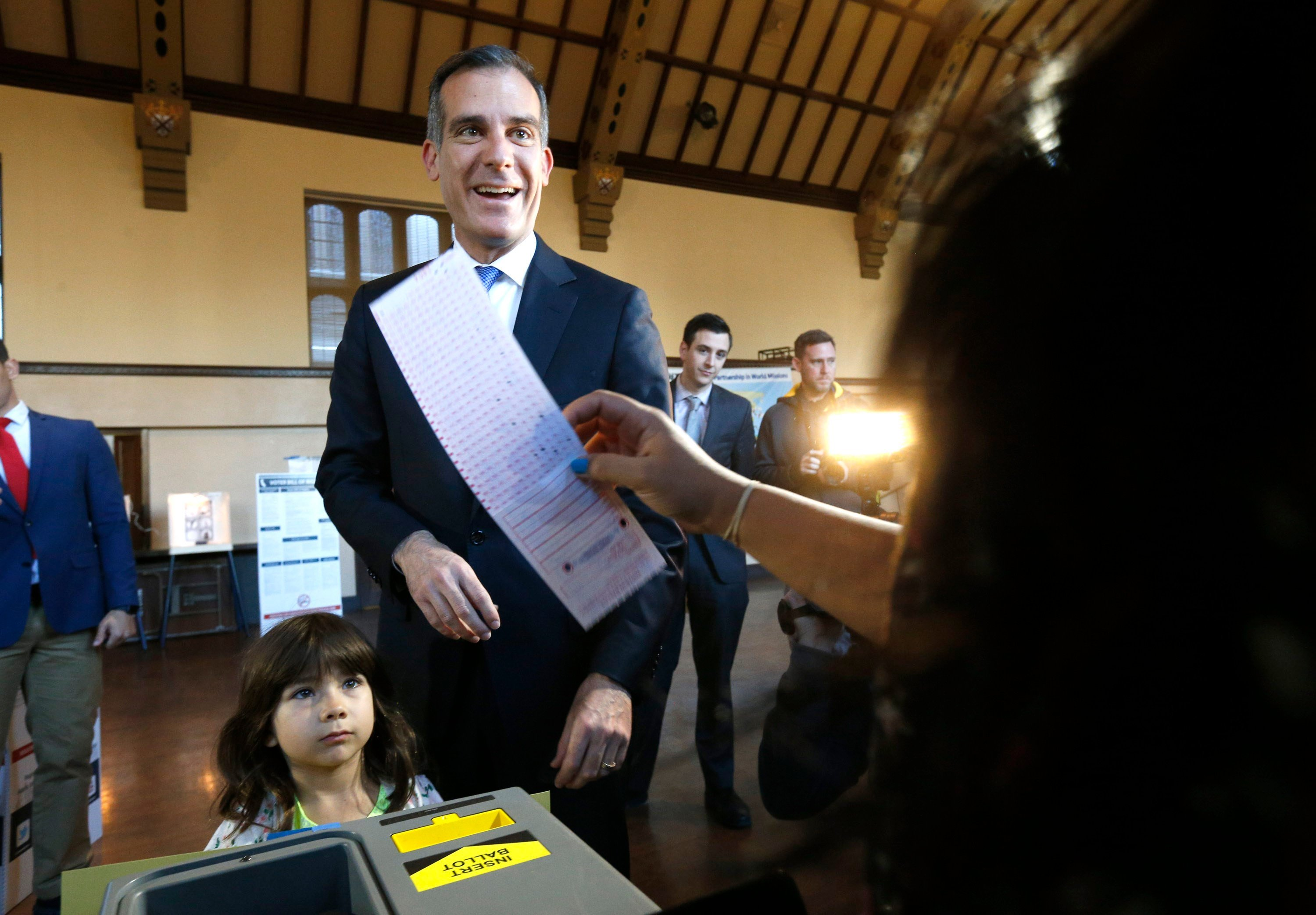 Los Angeles Mayor Eric Garcetti casts his election ballot with his daughter Maya in Los Angeles, on Tuesday, March 7, 2017. (AP Photo/Nick Ut)