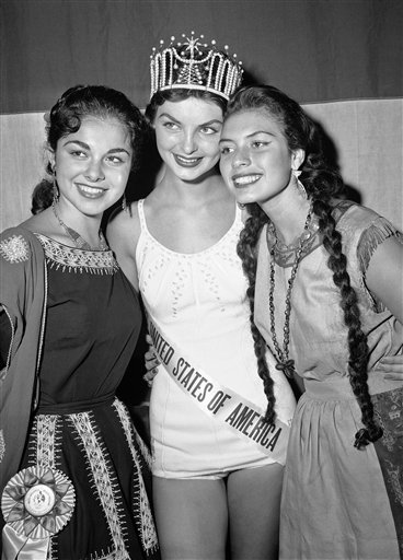 FILE - This July 17, 1957 file photo shows two foreign entrants in the Miss Universe Contest, Miss Israel, left, Atara Barzely, and Miss Peru, Gladys Zender, congratulating the new Miss U.S.A., Leona Gage, center, after the Maryland beauty won her title.