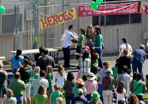 Carlos Partida, center left, embraces Kelly Elementary School principal Tressie Armstrong, during a gathering at the school Monday, Oct. 11, 2010, in Carlsbad, Calif.