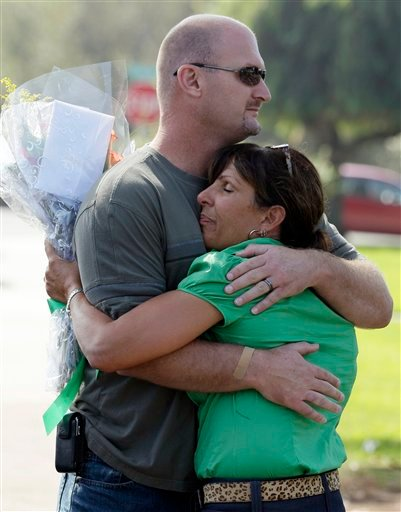 Kelly Elementary School principal Tressie Armstrong, right, hugs a parent as families arrive to school with their children.