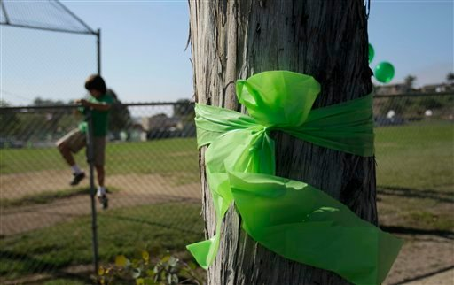 A boy climbs a fence at Kelly Elementary School to put up a balloon behind a green bow tied around a tree at the school.