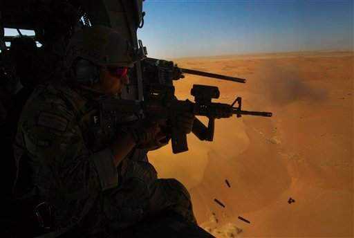 Alejandro Serrano from the 46th Expeditionary Rescue Squadron, and a machine gunner next to him, test fire their weapons in the open desert of Afghanistan's Kandahar province on Monday Oct. 11, 2010.(AP Photo/David Guttenfelder)