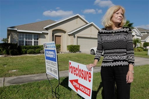 In this Oct. 6, 2010 photograph, realtor Dorothy Buse stands in front of a foreclosed home in Kissimmee, Fla. Foreclosed homes have now been frozen as banks and mortgage companies review their procedures. (AP Photo/Phelan M. Ebenhack)
