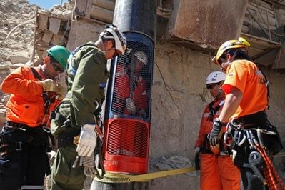 Rescue workers stand next to a colleague who is inside a capsule after performing a dry run test for the eventual rescue of the 33 miners trapped at the San Jose mine, near Copiapo, Chile, Monday, Oct. 11, 2010.