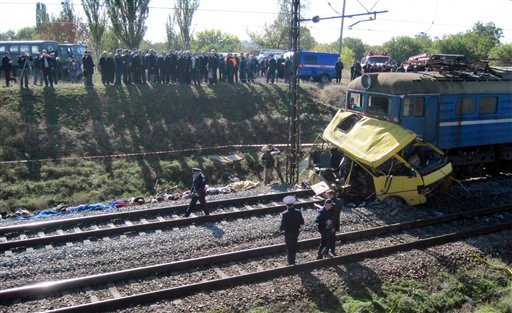 The remains of a bus lay next to a railway train at the site of an accident outside the town of Marhanets, Ukraine, Tuesday, Oct. 12, 2010. (AP Photo)