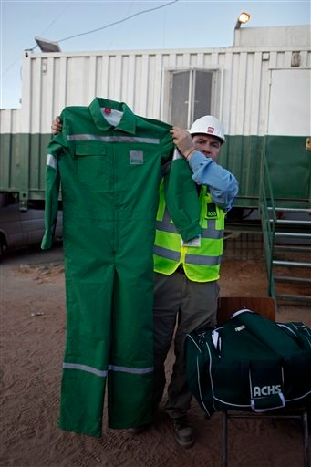 A man working on the rescue of the 33 miners trapped at the San Jose mine, shows one of the overalls that will be worn by the miners during their rescue operation outside the mine, near Copiapo, Chile, Monday, Oct. 11, 2010.