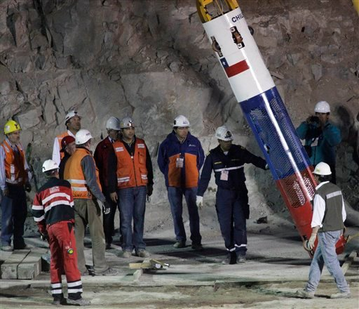 Rescue workers and officials test the rescue capsule that will be used to extract the 33 trapped miners one by one at the San Jose Mine near Copiapo, Chile, Tuesday Oct. 12, 2010.