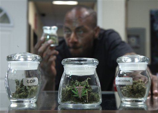 In this Sept. 21, 2010 file photo, medical marijuana patient Ezekiel Muses, who uses the drug for back pain, checks out a jar of medical marijuana at the CANNA CARE medical marijuana shop in Sacramento, Calif.