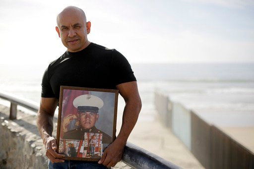 In this Feb. 13, 2017 image photo, U.S. Marine Corps veteran Antonio Romo holds a picture of himself taken from his days at boot camp, as he poses for a portrait next to the U.S. border wall on the beach in Tijuana, Mexico.