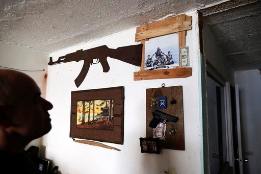 In this Feb. 13, 2017 photo, U.S. Marine veteran Antonio Romo looks at a replica of a pistol and other military items from his time in the service, mounted on his apartment wall in Tijuana, Mexico.