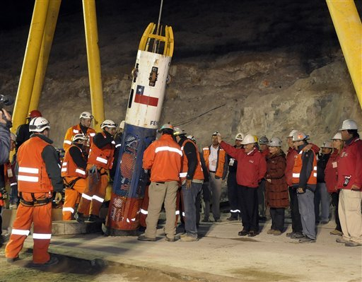 Chilean President Sebastian Pinera, in red jacket next to the capsule, and other officials and rescue workers greet as rescue worker Manuel Gonzalez Paves is lowered in the capsule into the mine where miners are trapped to begin the rescue.