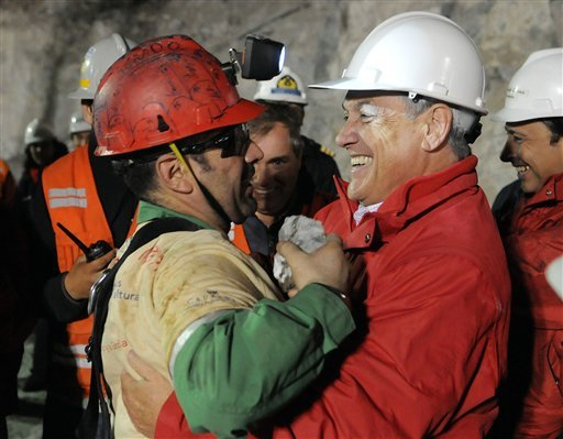In this photo released by the Chilean presidential press office, Chile's President Sebastian Pinera, right, hugs rescued miner Mario Sepulveda after Sepulveda was rescued from the collapsed San Jose gold and copper mine.