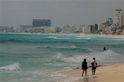 A couple walks on the beach in Cancun, Mexico, a few hours before the estimated arrival of hurricane Paula to Mexico's Yucatan peninsula, Tuesday, Oct. 12, 2010. (AP Photo/Israel Leal)