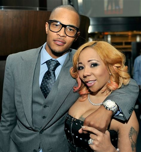 """Grammy award winning artist Clifford """"TI"""" Harris, left, speaks with media with his wife Tameka """"Tiny"""" Harris, during an Alzheimers """"For the Love of Our Fathers"""" foundation honoree luncheon at the Luckie Lounge Sunday, Oct. 3, 2010, in Atlanta."""