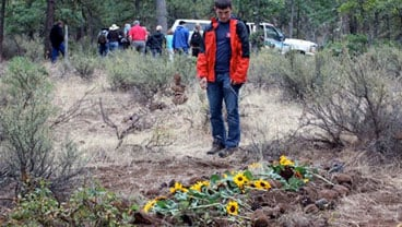 In this photo taken Saturday, Sept. 18, 2010, David Sall stands at his father's grave at the White Eagle Memorial Reserve outside Goldendale, Wash., moments after the funeral service ended. (AP Photo/Manuel Valdes)