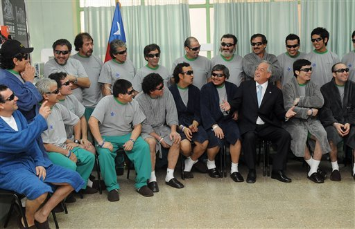 In this photo released by the Chilean Presidential Press Office, Chile's President Sebastian Pinera, third right front row, jokes with a rescued miner during a visit to the hospital where the 33 miners are undergoing a medical check ups.
